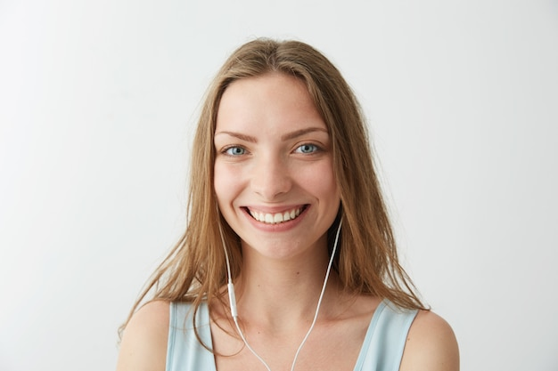 Tender young pretty girl smiling listening to streaming music in headphones .