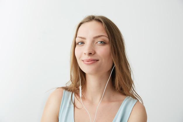 ヘッドフォンでストリーミング音楽を聴いて笑って優しい若いきれいな女の子。