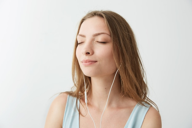 ヘッドフォンで音楽をストリーミングして聞いて目を閉じて笑っている優しい若いかわいい女の子。