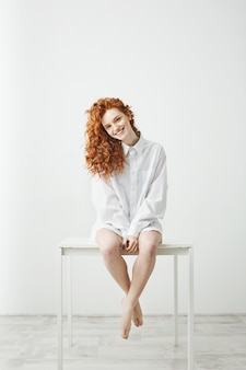 Tender young redhead woman in shirt sitting on table smiling looking at camera.