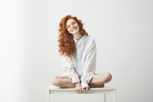 Tender young redhead woman in shirt smiling sitting on table posing.