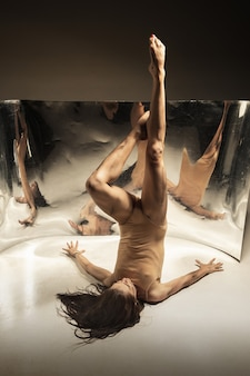 Tender. young, stylish modern ballet dancer on brown wall with mirror, illusion reflections on surface. magic of flexibility and motion. concept of creative art dancing, action and inspiring.