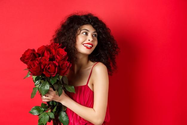 우아한 빨간 드레스에 부드러운 젊은 여자, 빨간 장미의 낭만적 인 꽃다발을 들고 오른쪽 찾고, 꿈꾸는 미소, 발렌타인 데이, 스튜디오 배경에 연인에 대해 생각.