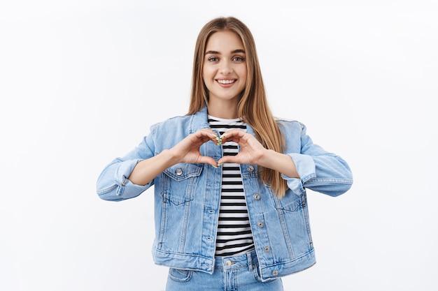 愛の優しい若い女性は同情を告白し、心のジェスチャーと笑顔を示し、ロマンチックなカメラを見て、製品や人のような何かを崇拝し、陽気な白い壁に立っています