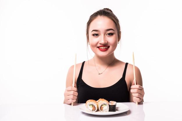 La giovane donna tenera è seduta al tavolo bianco e ha un piatto con sushi con bacchette di legno in entrambe le mani