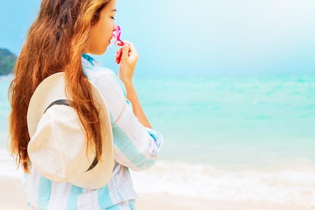 Tender young woman smells tropical flower frangipani