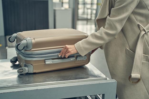 プロのコントロールのために彼女の荷物を準備しながらセミポジションに立っている優しい若い女性