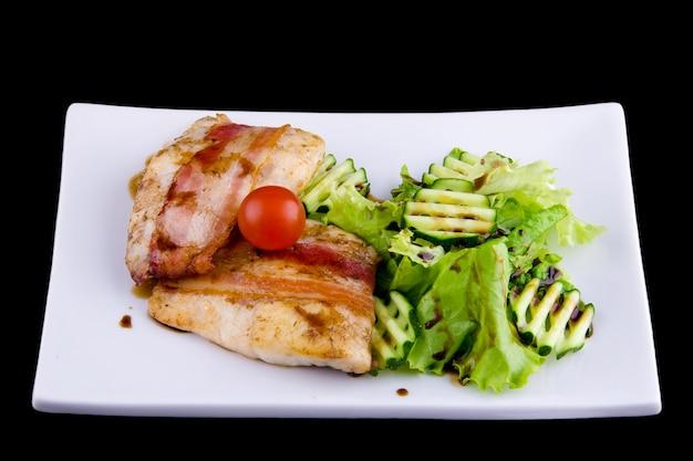 베이컨의 부드러운 잰더: 필레, 훈제 베이컨, 석류 소스 narsharab, 오이, 양상추 잎. 검은 배경에 흰색 접시에 가까이
