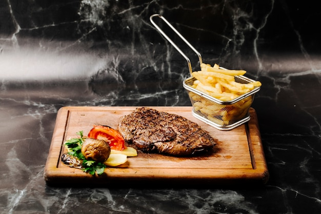 Tenderloin steak with grilled vegetables and french fries on a wooden board.