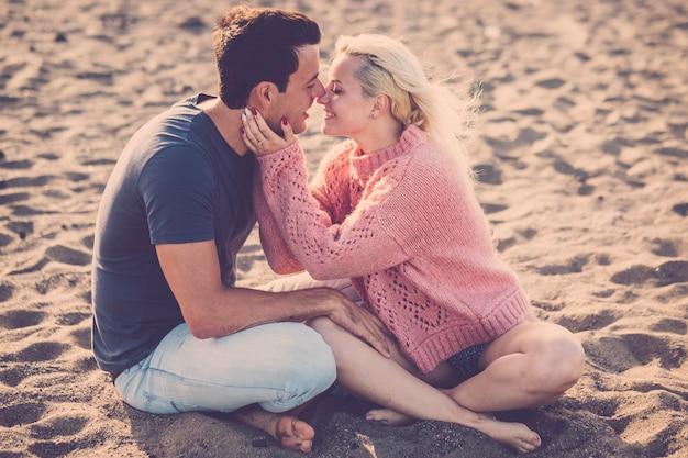 素敵な美しいモデルのカップルのための休暇中にビーチに座って優しさの活動 Premium写真