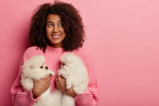 優しさ、動物の世話と人々の概念。女の子のペットの飼い主は、ふわふわのかわいい子犬2匹とポーズをとり、友好的な関係を築いています