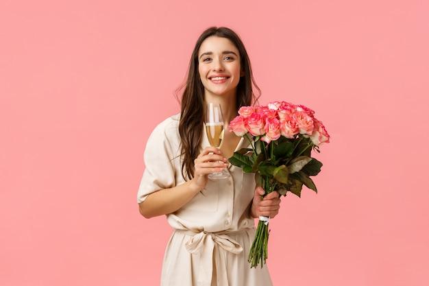 Концепция нежности, красоты и торжества. элегантная и чувственная женственная леди, держащая красивые цветы и бокал шампанского, наслаждающаяся вечеринкой, днем рождения, получая красивые розы, улыбаясь