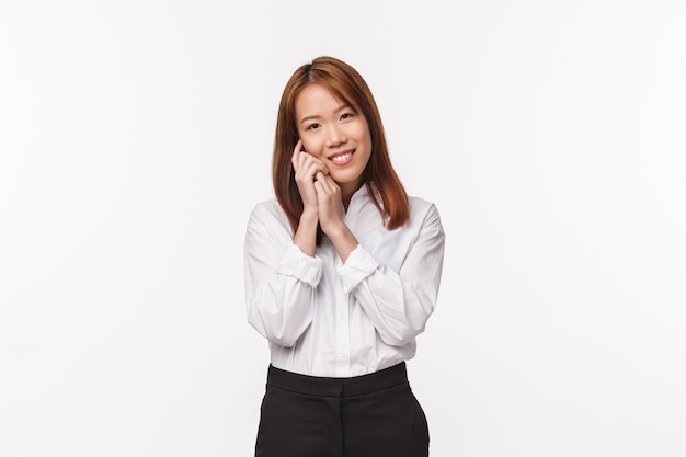 Tenderness, beauty and business concept. tender charming asian woman, office lady in white shirt and black skirt, softly touching her face and smiling delighted, apply make-up, skincare routine