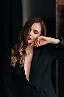 Нежная мечтательная девушка с красными губами позирует с закрытыми глазами и улыбкой и готовится к дню святого валентина