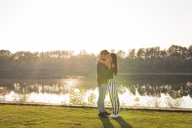 Tenderness, love and nature concept - beautiful woman and handsome man hugging over water background