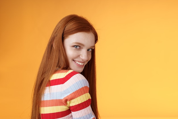 優しさ、ロマンス、誘惑の概念。魅力的な生意気な軽薄な若い赤毛の大胆な女の子は、後ろを向いて肩のカメラを見て、愚かなコケティッシュなクスクス笑いを表現します。