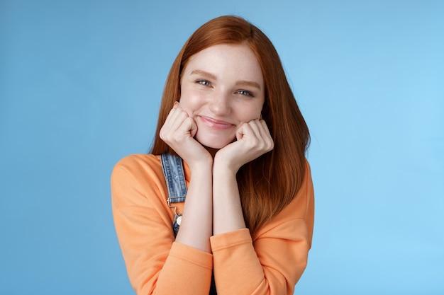 Нежность благополучие красотка привлекательная молодая рыжая девушка чистая кожа голубые глаза поджарые ладони глупо улыбающийся камера смотреть весело с энтузиазмом слушать интересные истории с удовольствием синий фон