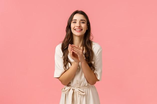 優しさ、女性、美容のコンセプトです。巻き毛の陽気な魅力的な若いかわいいブルネットの少女、服を着る日付を取得、手のひら胸を柔らかく、触れて笑って、感謝して、ピンクの壁