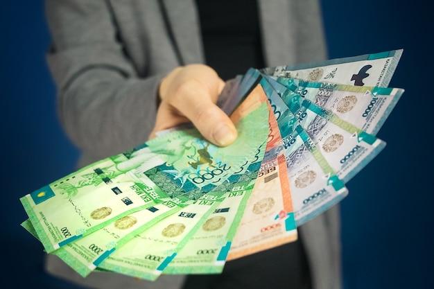 Тенге национальная валюта казахстана в руке. крупный план, выборочный фокус.