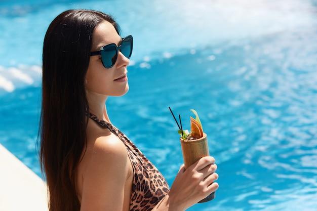 ヒョウ柄の水着と黒のサングラスで美しい女性を締め