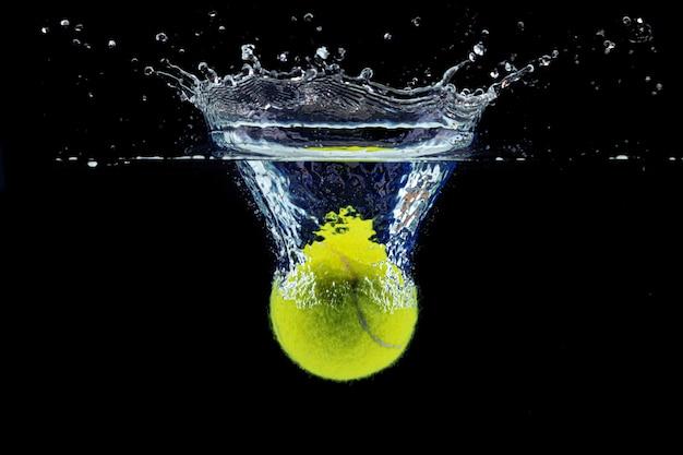 Теннисный мяч падает в воду с всплеском на темно-черном фоне