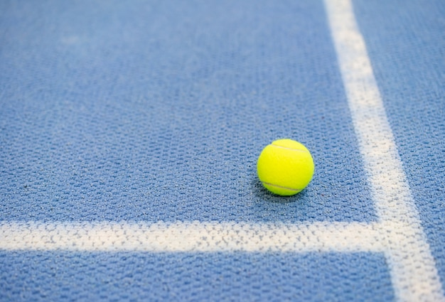 Tennis ball indoor on tennis court, white line, blue surface, copy space