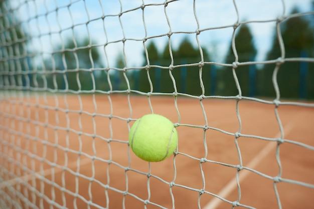 テニスボールがネットに当たっている