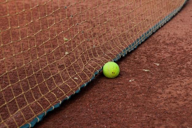 Теннисный мяч у сетки фрагмент открытого теннисного корта с глиняным покрытием