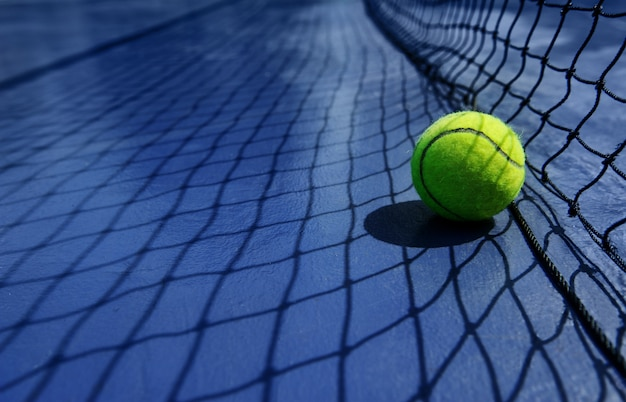 Tennis ball leaning agaist the net court