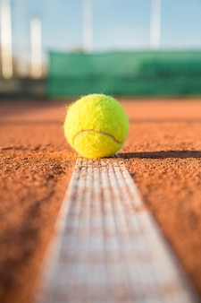 Tennis ball lying on white line on tennis court on sunny day.