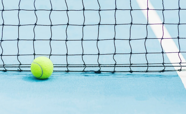 Tennis ball with black screen net background on hard blue tennis court