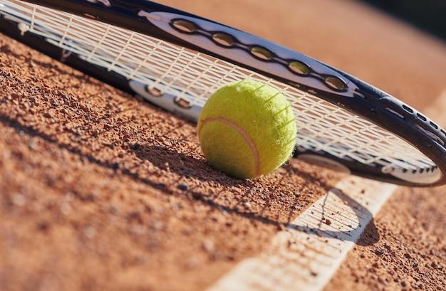 Теннисные мячи и ракетки на глиняном корте