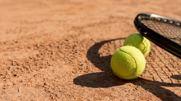 Tennis balls and black racket