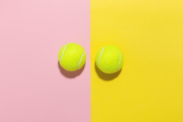 テニスボールフラットピンクと黄色の上に横たわる Premium写真