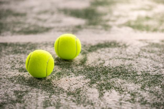 Tennis balls on a padel court indoors.