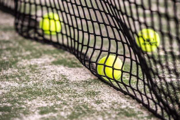 Tennis balls behind padel net indoors.