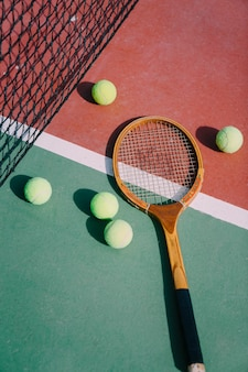 Tennis balls and racket on court