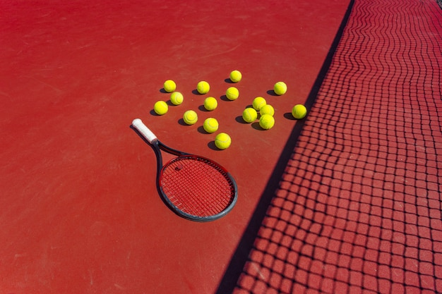 Tennis balls and racket on the grass court