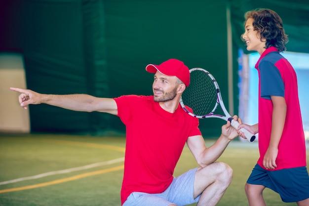 テニス。赤い帽子をかぶったコーチとジムでテニスラケットを持った少年