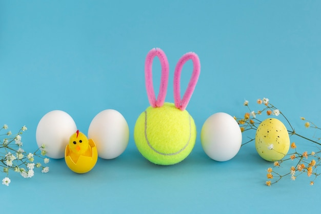 Tennis easter with smiley tennis ball with bunny ears, white chicken eggs and gypsophila on blue background.