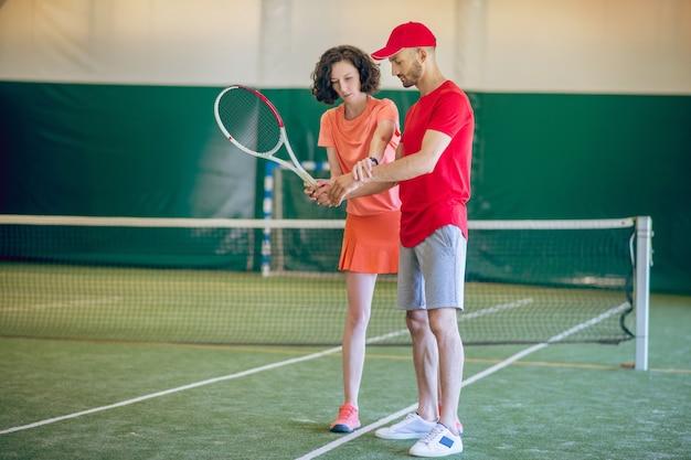 테니스. 빨간 모자와 그의 여성 코치와 함께 운동을하는 라켓을 가진 남자