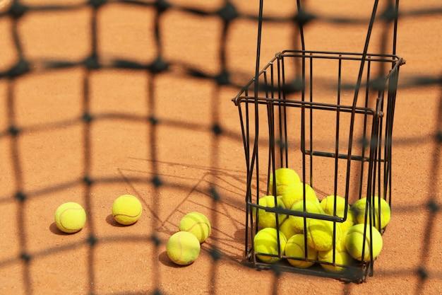 Теннисная сетка против грунтового корта с корзиной с мячами