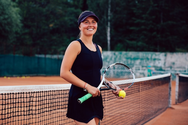 Tennis player. attractive joyful girl, standing with racket and tennis ball on the court