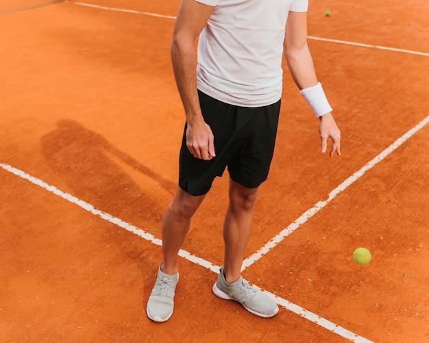 ボールをバウンスしているテニス選手 無料写真