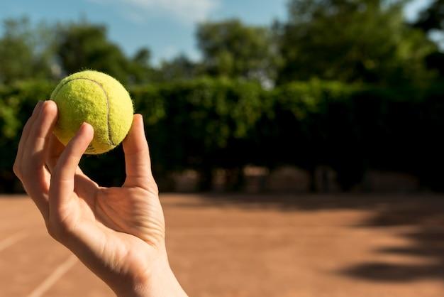 Tennis player grabbing a tennis ball