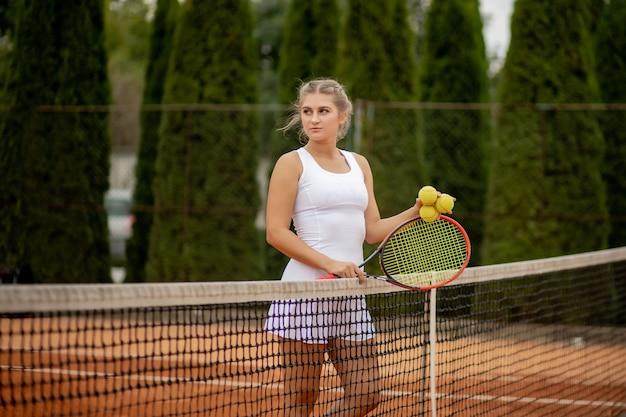 Теннисист. счастливая девушка, стоя с ракеткой и теннисным мячом на корте, возле сетки