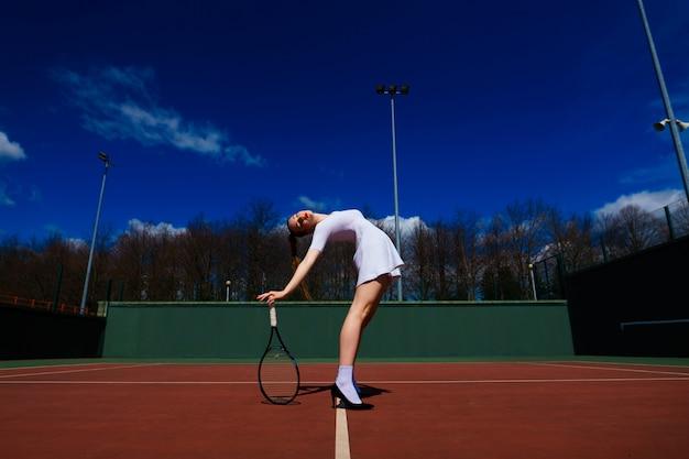 白いドレスとコートでテニスラケットを保持しているハイヒールのテニス選手