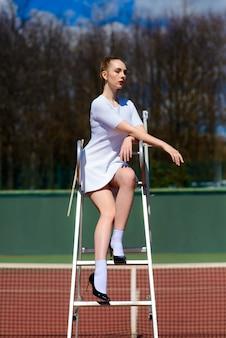 審判のスポットで白いドレスとハイヒールのテニス選手