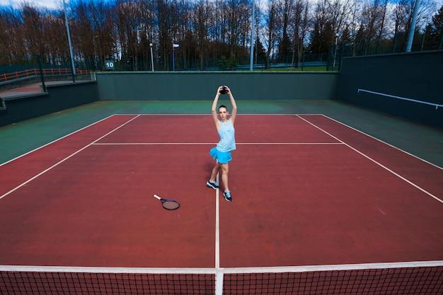 白いドレスとコートでテニスラケットとハイヒールのテニス選手
