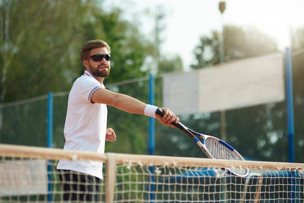 The tennis player is wearing sunglasses